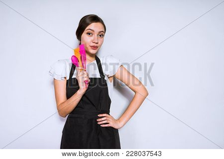 Cute Young Girl Cook In Black Apron Holding Tools For Cooking