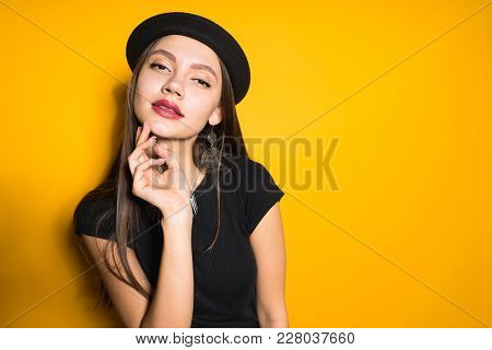 Attractive Young Woman In Black Dress And Fashionable Hat Posing On Yellow Background