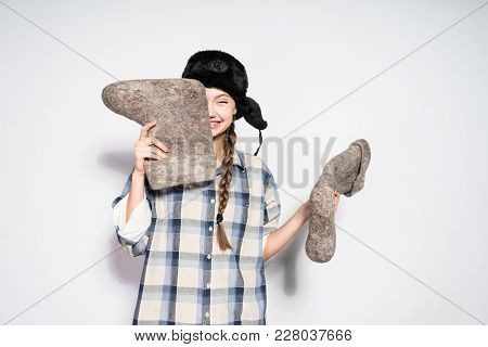 Laughing Young Russian Girl In A Hat With Ear-flaps Holds Gray Felt Boots In Hands