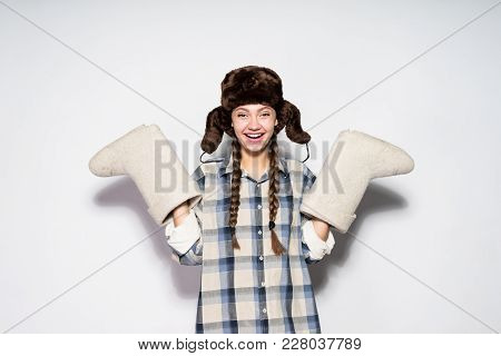 Happy Beautiful Russian Girl In A Cap With Ear-flaps Holds Warm Gray Felt Boots, Laughs