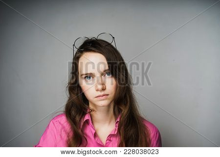 Sad Young Girl Office Worker In A Pink Shirt Looking At The Camera