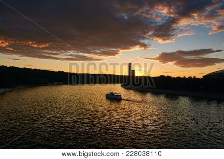 Aerial Cityscape At Sunset With Tour Boat Traffic On River At Foreground And Dramatic Clouds At Back