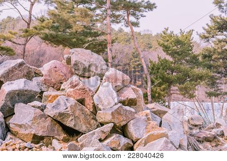 Closeup Of Large Pile Of Boulders In Countryside With Evergreen Trees In Background