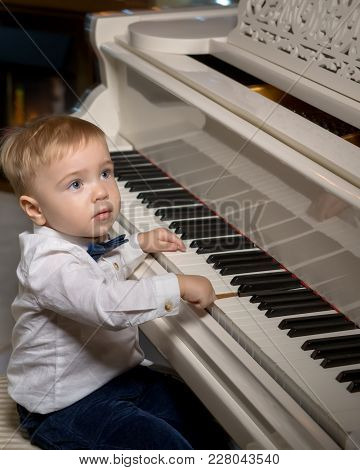 Happy Little Boy Playing On The Piano. Keyboard And Notes. Concept Of Educational Illustration Of Mu