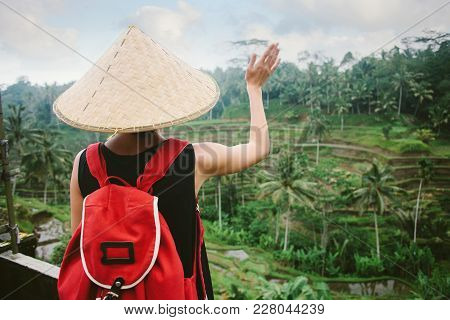 Young Lady With Traditional Asian Hat And Backpack Looking At Rice Field