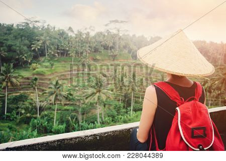 Young Lady With Traditional Asian Hat And Backpack Standing Near Rice Field, Intentional Sun Glare A