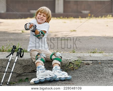 Young Roller Skater Taking Off His Protection Equipment After Skating