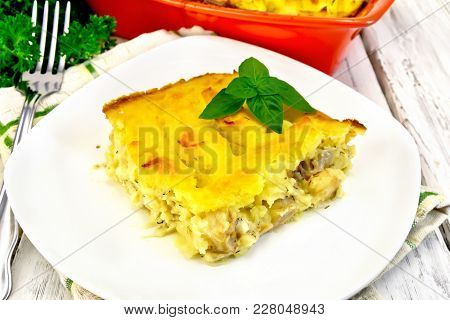 Casserole From Mashed Potatoes With A Fish Fillet In A Plate On A Towel On A Wooden Board Background