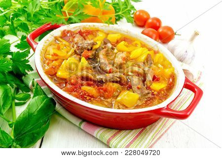 Ragout Of Turkey Meat, Tomato, Yellow Sweet Pepper And Onion With Sauce In A Red Brazier On A Napkin