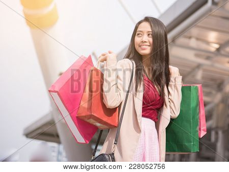 happy young women show shopping bag, sale, consumerism and people concept. fashion tone.