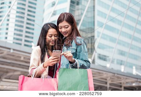 Happy two young beautiful women using mobile phone or smart phone in modern city, shopping consumeri