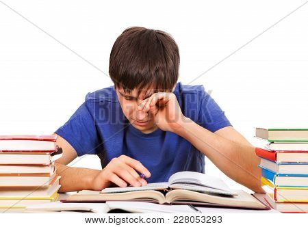 Tired Student Rub An Eyes On The School Desk Isolated On The White Background