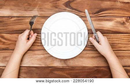 Hungry Child Waiting For Meal. Child's Hands Holding Fork And Knife Over Table With Empty Dish. Top
