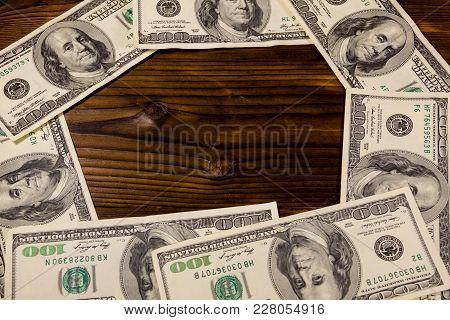 Frame Of Hundred Dollar Bills On Wooden Background