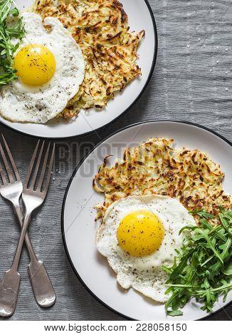 Large Potato Latkes, Fried Egg, Arugula - Tasty Breakfast Or Snack On A Gray Background, Top View