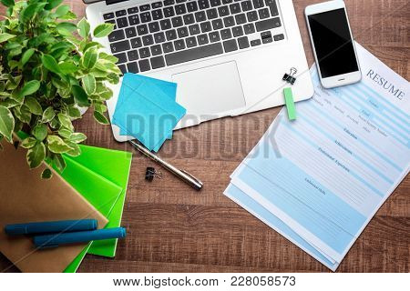 Resume forms with laptop and office stationery on table. Job interview concept