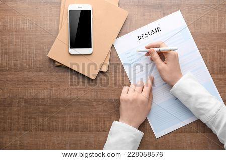 Woman filling in resume form at table. Job interview concept