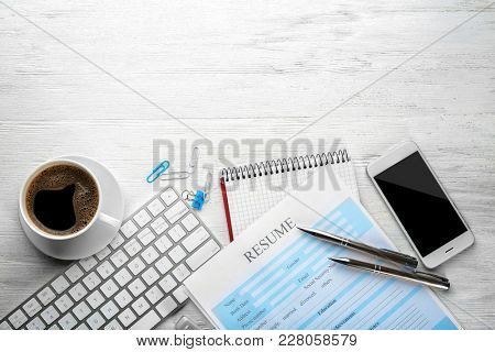 Phone with computer keyboard and resume form on table. Job interview concept