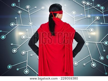 Digital composite of Back of business woman superhero with hands on hips against network and flares
