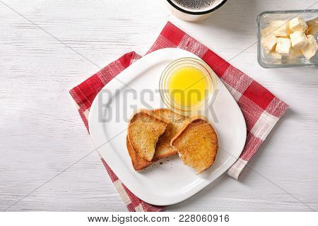 Plate with tasty toasted bread and melted butter on table