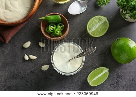 Tasty creamy lime sauce for fish taco in glass jar on kitchen table