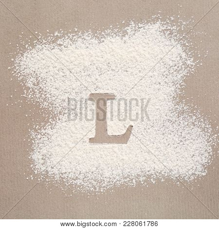 Silhouette of letter L on scattered flour