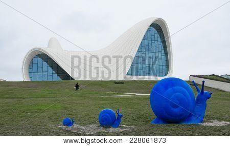 Baku, Azerbaijan - January 01, 2018: Big blue coloured snails on green grass in front of famous Heydar Aliyev Center, Baku, Azerbaijan