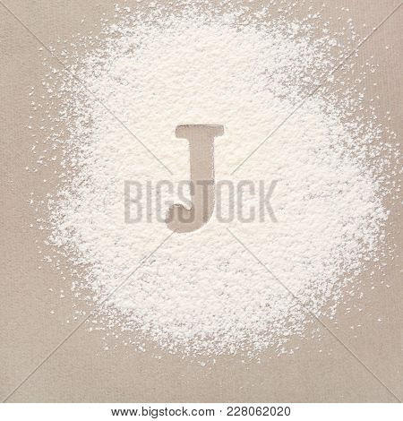 Silhouette of letter J on scattered flour