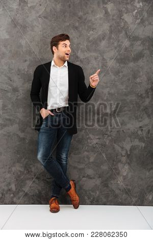 Image of shocked young businessman standing over grey wall background looking aside pointing.