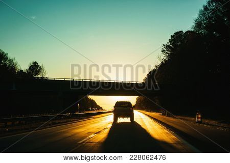 SUV driving into the sunset, sun hidden by bridge
