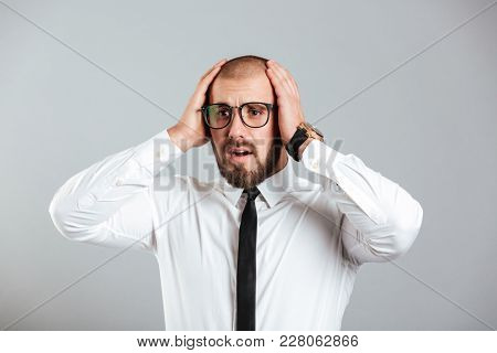 Image of adult man 30s in white shirt and eyeglasses grabbing his head expressing problem or failure isolated over gray background