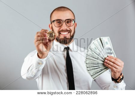Photo of economist man in glasses and suit showing bitcoin in focus and holding lots of money dollar currency isolated over gray background