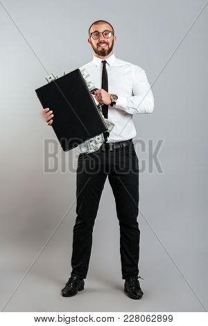 Rich man entrepreneur in glasses and business suit holding diplomat full of dollar money isolated over gray background