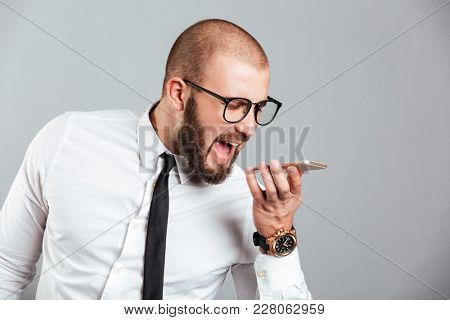 Portrait of a furious businessman yelling at mobile phone isolated over gray background