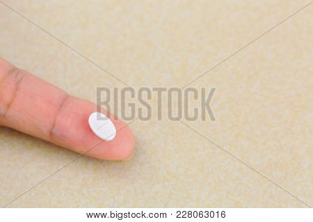 Anti anxiety white pill medicine on finger with blurred yellow background and copyspace