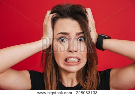 Portrait closeup of nervous woman grabbing her head and expressing problem or fright isolated over red background