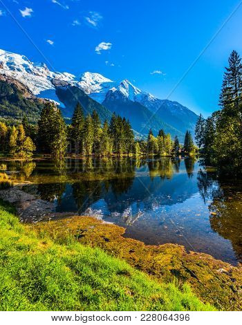 The lake reflects the snowy mountains and the blue sky. Chamonix City Park is illuminated by sunset. Sunny autumn day in the French Alps. Concept of active winter tourism