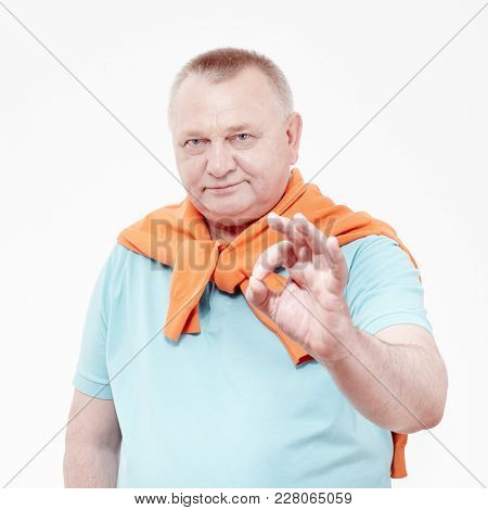 Mature man wearing blue shirt and draped over his shoulders orange jumper showing A-ok hand gesture against white wall - success concept