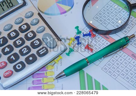 Above Lies The Pen, Magnifier And Calculator. Analyzing Financial Data And Counting On Calculator