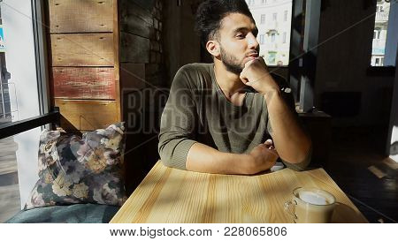 Arab Guy Sits Near Cup Of Coffee, Put Elbows On Table In Caf . Man Nod And Listening Waitress. Hands