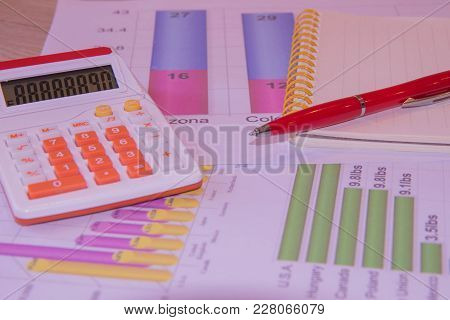 The Documents Painted Colorful Graphics. Above Lies The Pen, Notebook And Calculator. Analyzing Fina