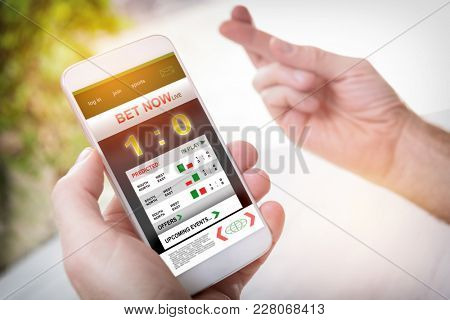 Betting on sports, holding smart phone with working online betting mobile application, crossed fingers used to wish for luck
