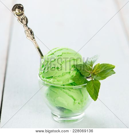 Cup of honeydew ice cream on wooden background.