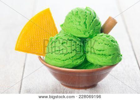 Honeydew ice cream in bowl on wooden background.