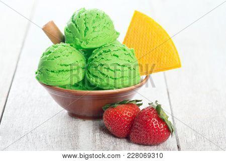 Scoop of honeydew ice cream in bowl on wooden background.