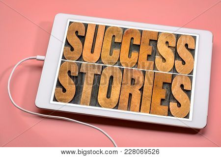 success stories typography - word abstract in vintage letterpress wood type on a digital tablet
