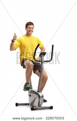 Young man exercising on a cross-trainer machine and making a thumb up gesture isolated on white background