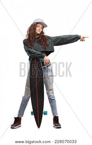Full length portrait of a teenage skater girl posing with a longboard and pointing isolated on white background