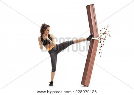 Full length profile shot of a girl kicking and breaking a chocolate bar isolated on white background