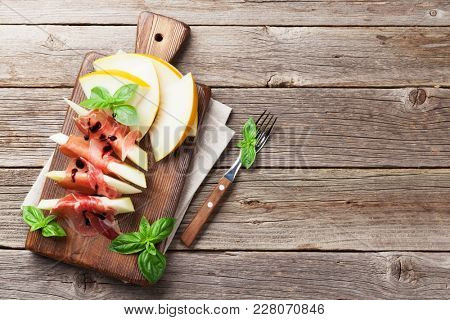 Fresh melon with prosciutto and basil. Antipasti. On wooden table with copy space for your text